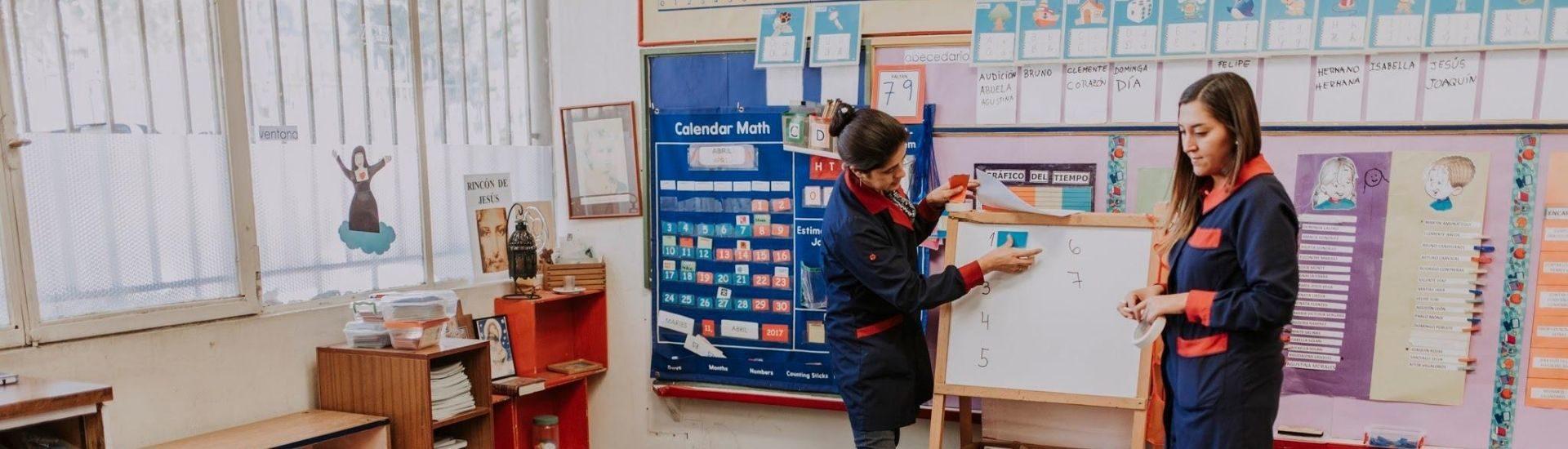 Foto de profesoras en la sala de clases utilizando la pizarra