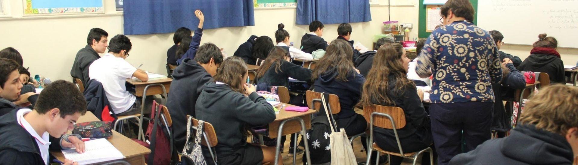 Estudiantes escribiendo en sus cuadernos en la sala de clases