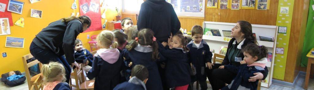 Foto de educadoras junto a niñas y niños que las abrazan