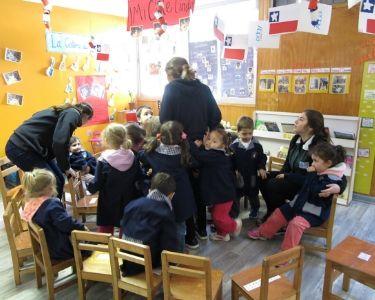 Foto de educadoras junto a niños y niñas en la sala de un jardín infantil