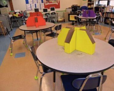 Foto de truco de archivadores de colores en medio de cada una de las mesas para que las y los estudiantes dejen sus trabajos