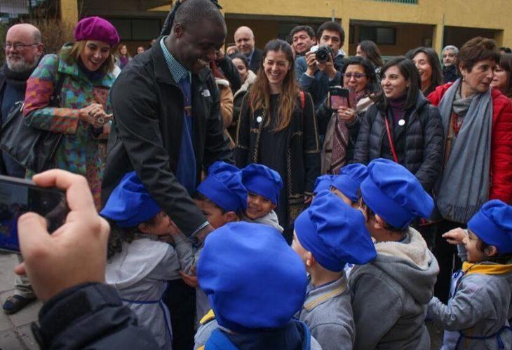 Foto de Peter Tabichi con estudiantes chilenos