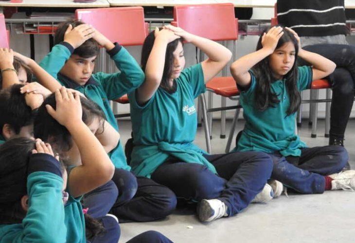 Foto de estudiantes con los brazos en la cabeza
