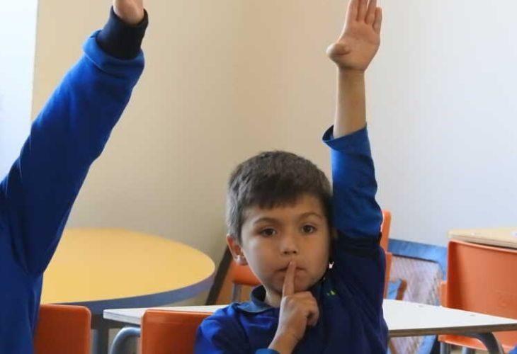 Foto de estudiantes levantando la mano