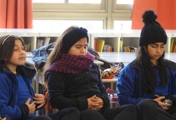 Foto de estudiantes sentadas cerrando los ojos