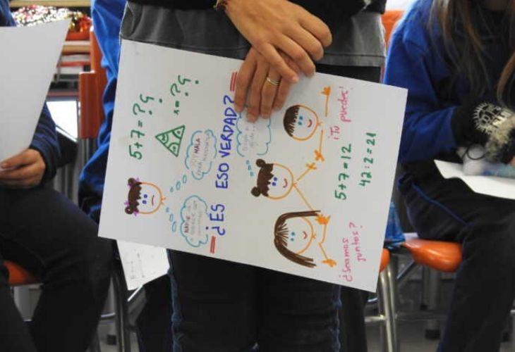 Foto de profesora sosteniendo un afiche