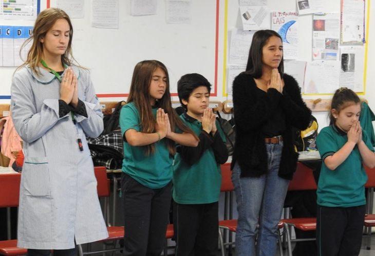 Foto de profesoras y estudiantes cerrando los ojos