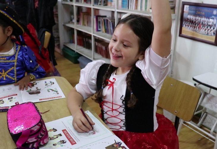 Foto de una estudiante levantando la mano