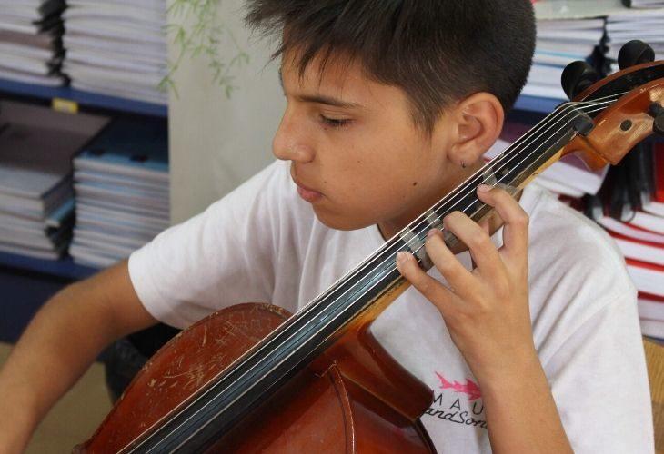 Foto estudiante tocando un instrumento