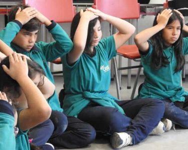 Foto estudiantes participando de una actividad con las manos en la cabeza