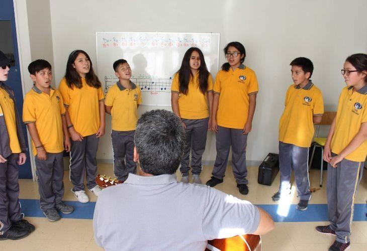 Foto profesor tocando la guitarra y sus estudiantes cantando
