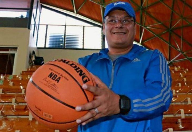 Profesor Sergio Ramírez sosteniendo una pelota en un Gimnasio