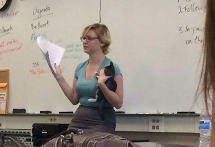 Profesora con un gato en brazos mientras realiza su clase