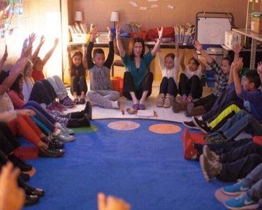 Profesora junto a sus estudiantes sentados y sentadas en el suelo y levantando los brazos