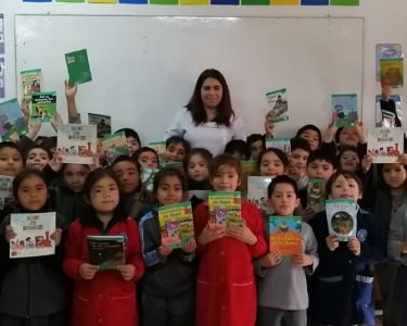Profesora y estudiantes con libros en la mano