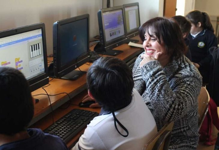 Profesora Samanta sonriendo junto a sus estudiantes en la sala de computadores