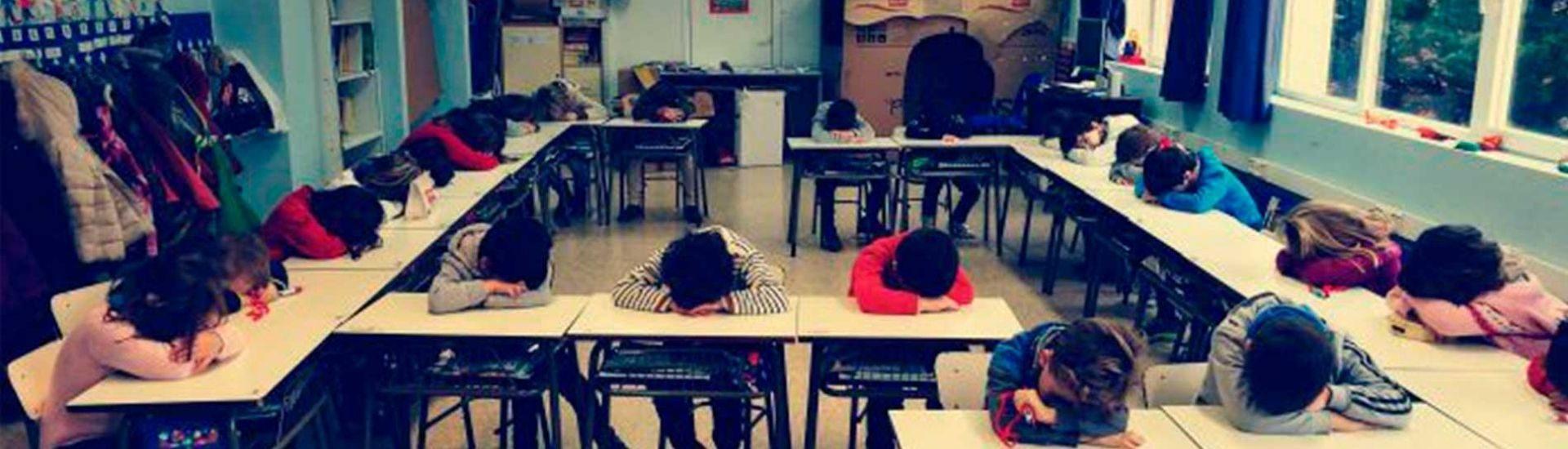 Foto de estudiantes apoyando su cabeza en las mesas de la sala de clases