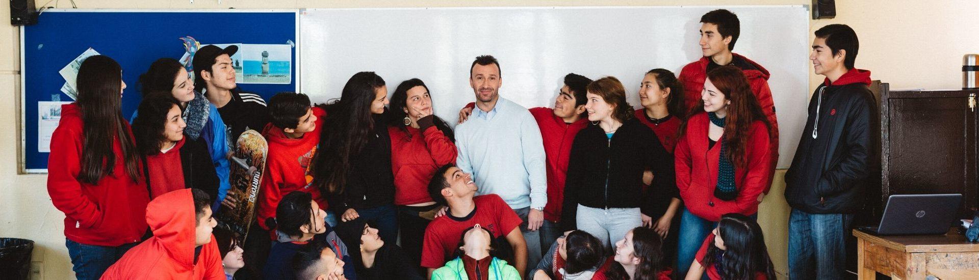 Imagen de un profesor en su sala de clases con sus estudiantes