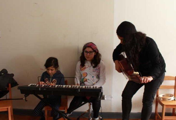 Profesora y estudiantes en el teclado y guitarra