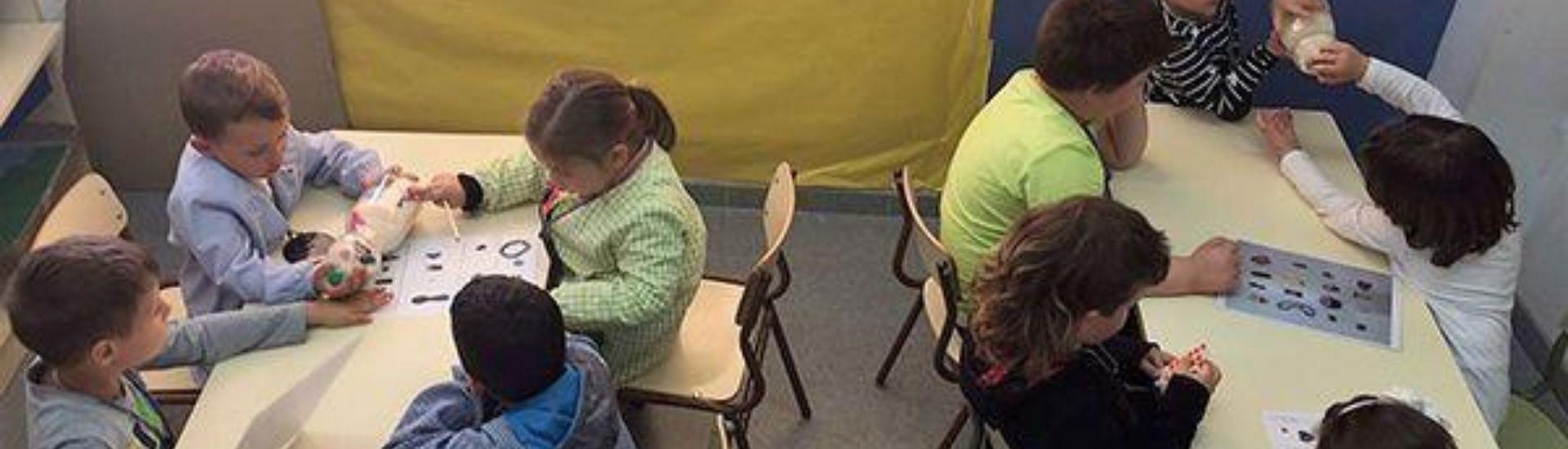 Estudiantes en la sala de clases leyendo con una botella