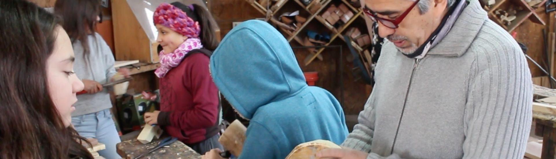 Docente y alumnos con modelando madera