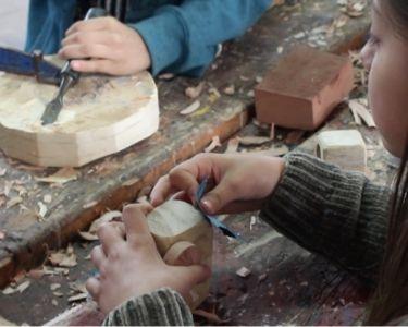 Niña modelando madera
