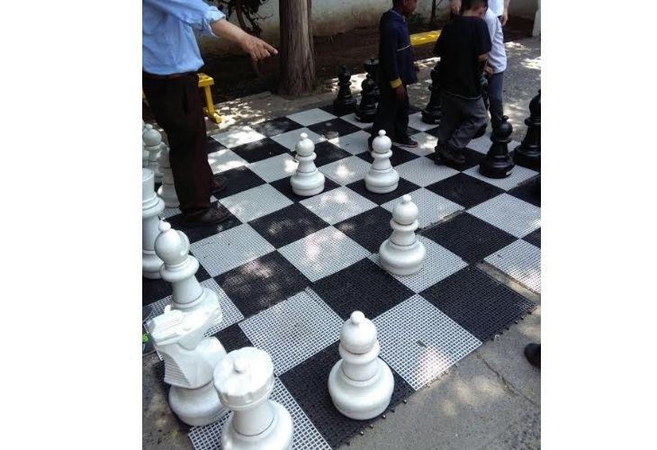 Foto de niñs jugando ajedrez gigante