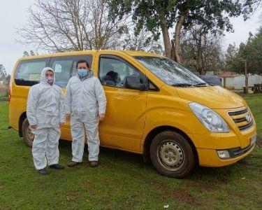 En la imagen se aprecia una fotografía en donde hay dos educadores vestidos con protección sanitaria y a sus espaldas se ve el furgón en el que llegan a escuelas rurales