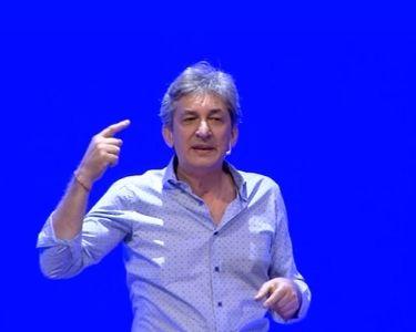 En la imagen se ve al centro a Sergio Federovisky con un fondo azul