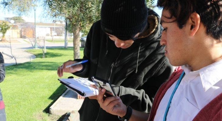 Dos estudiantes de Pablo Malhue haciendo anotaciones durante una clase en el exterior