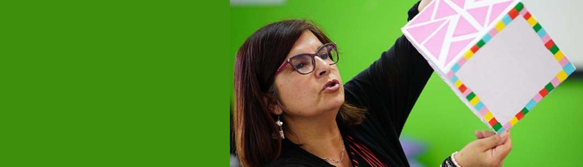 La docente finalista del GTO2020, Pamela Sánchez, dando una clase con un fondo de color verde.