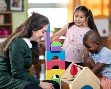 Imagen de una educadora en sala con dos estudiantes