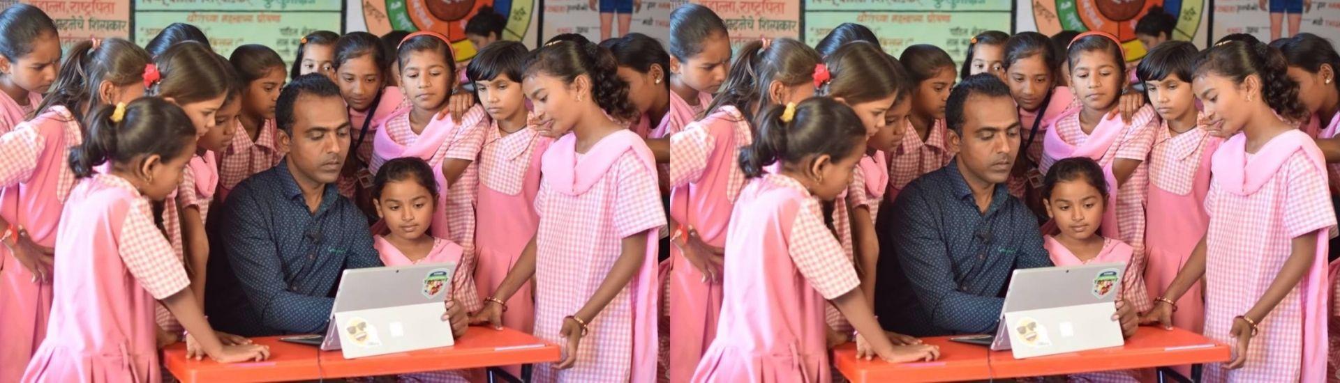 Una fotografía del profesor de la India, Ranjitsinh Disale, trabajando un texto con códigos QR junto a sus alumnas. Crédito: Global Teacher Prize