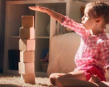 fotografía de niña haciendo una torre de bloques