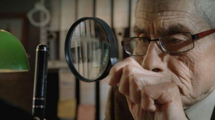 """Escena de Sergio con una lupa en el documental """"El agente topo"""""""