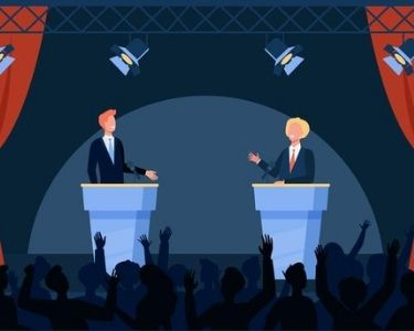 Dos personas hablando en un escenario y exponiendo para un público