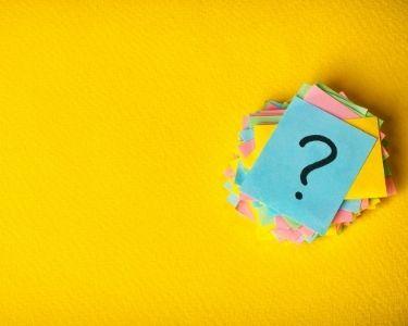 Imagen donde se ven varios papeles con signos de interrogación, para invitar a hacerse preguntas