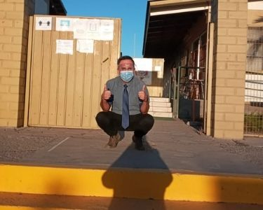 Rodrigo, profesor de tecnología, que trabaja desde la creación e innovación posando frente a su colegio en cuclillas