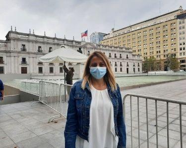 En la imagen se ve a la docente Paola Saavedra, creadora del canal de YouTube, en frente del Palacio de La Moneda en Santiago, Chile.