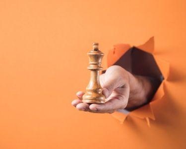 Fotografía de una mano con la pieza de un Rey en la mano. Imagen de Freepik. atravesando un papel, con un