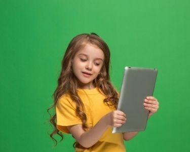 En la imagen se ve una niña delante de una pantalla verde, un gran recurso para tus estudiantes