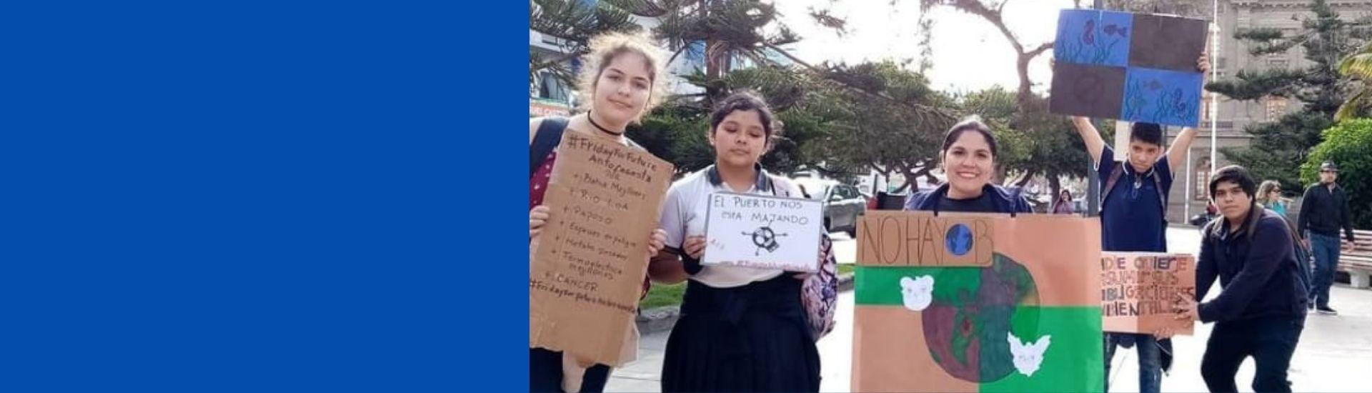 Profesora Mery con sus estudiantes realizando activismo medioambiental en la calle