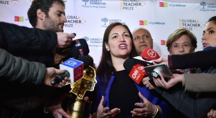 Imagen de Andria Zaforaku, profesora británica, rodeada de micrófonos de distintos medios chilenos