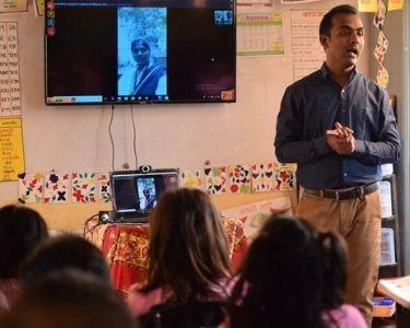 Fotografía de Ranjitsinh Disale en la sala de clases, junto a sus estudiantes en una clase. Ranjitsinh Disale se ve en el centro de la sala, conversando