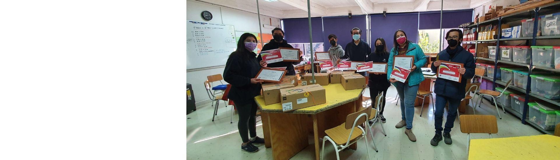 profesora con su equipo de rob[otica sosteniendo un diploa de primer lugar por ganar en una competencia