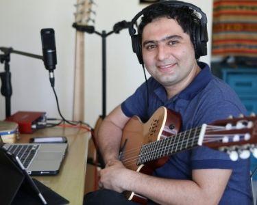 Retrato del profesor Cristóbal Rojas tomando una guitarra y mirando a la cámara, se trata del un profesor que dirige una orquesta de estudiantes ciegos o de baja visión